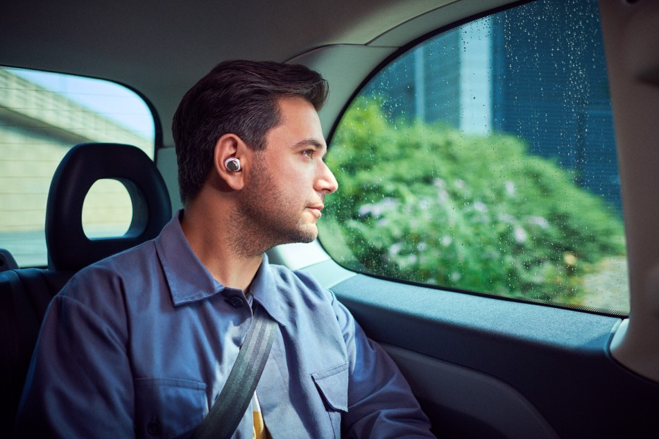 Man relaxes in car wearing Bowers & Wilkins PI7 earbuds