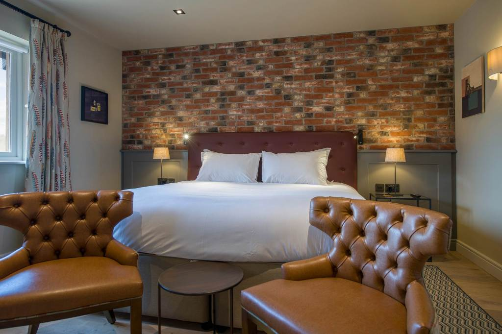 Modern bedroom at the Sandburn Hall Hotel with bare brick wall and white linen bed