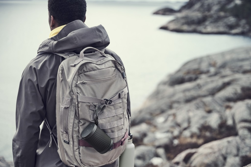 Beosund Explore wireless speaker hangs from the backpack of a hicker