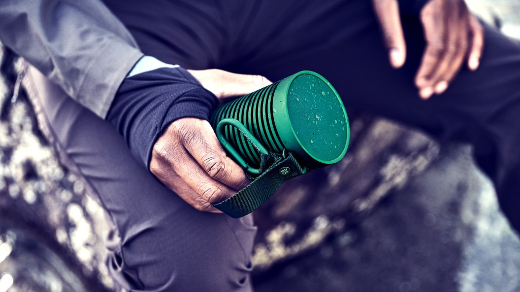 The Beosound Explore portable speaker held on a rocky outcrop