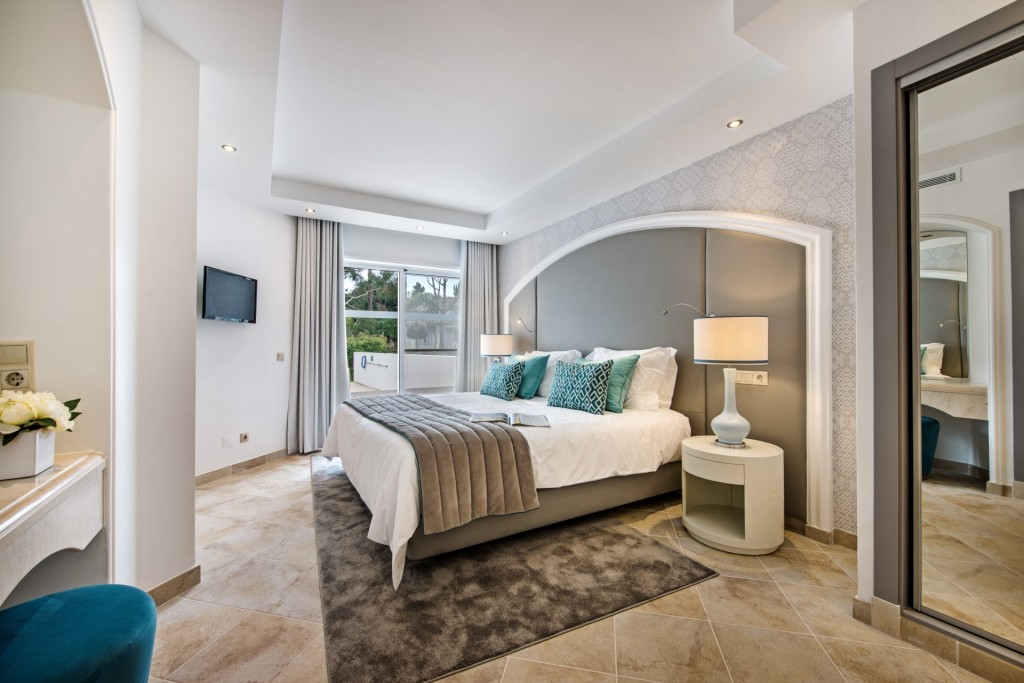 Interior view of a luxury bedroom suite in a refurbished villa at Four Seasons fairway, very bright with designer furnishings