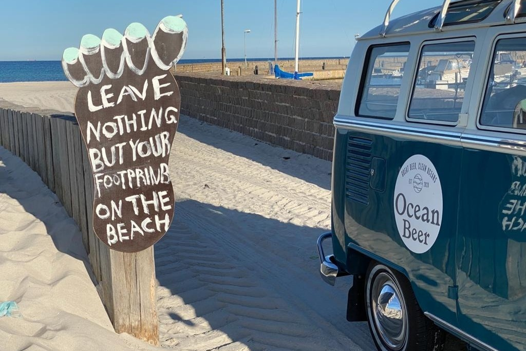 Ocean Beer car passing a sign on the beach says Leave Nothing But Your Footprints On The Beach