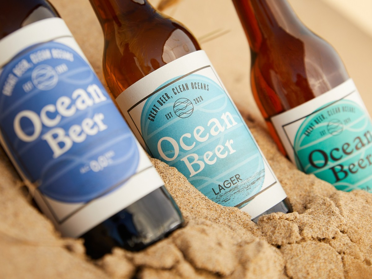 Three bottles of Ocean Beer in the sand on a beach