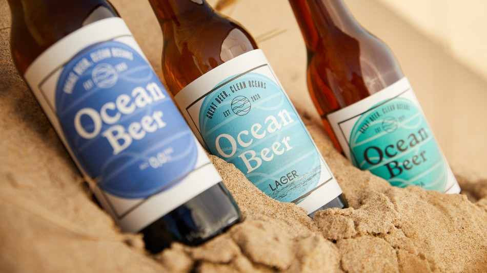 Three bottles of Ocean Beer in the sand on a beach