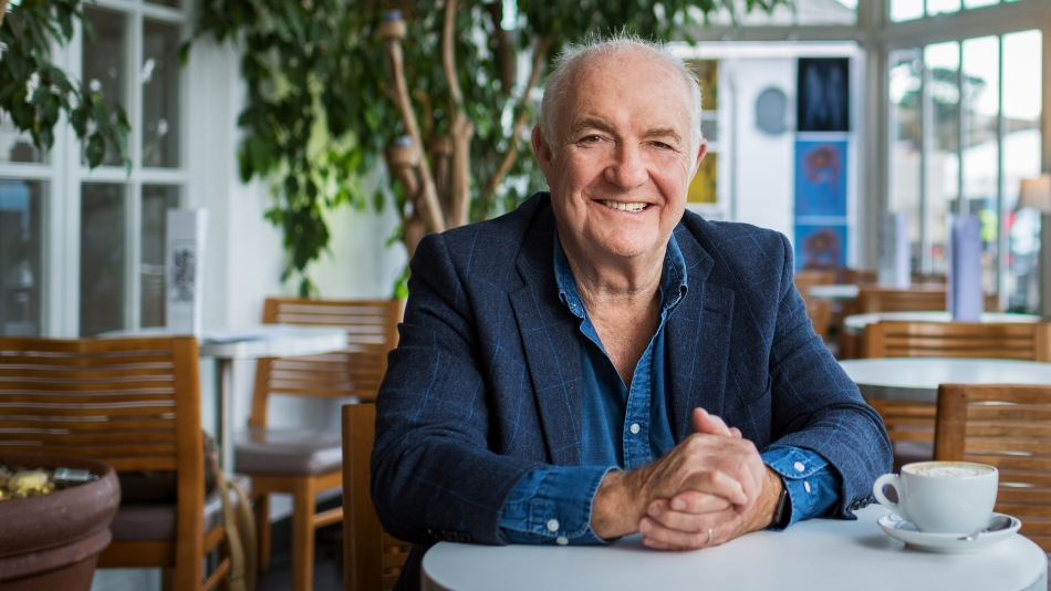 Cornish seafood chef Rick Stein sitting with a coffee