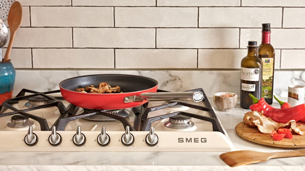 Red Smeg frying pan on a cooker surrounded by ingredients