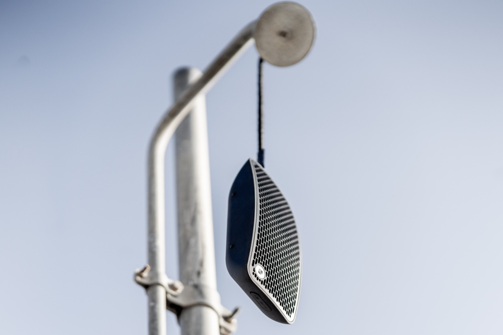 Audio Pro P5 hangs from a shower head on the beach by its wrist strap