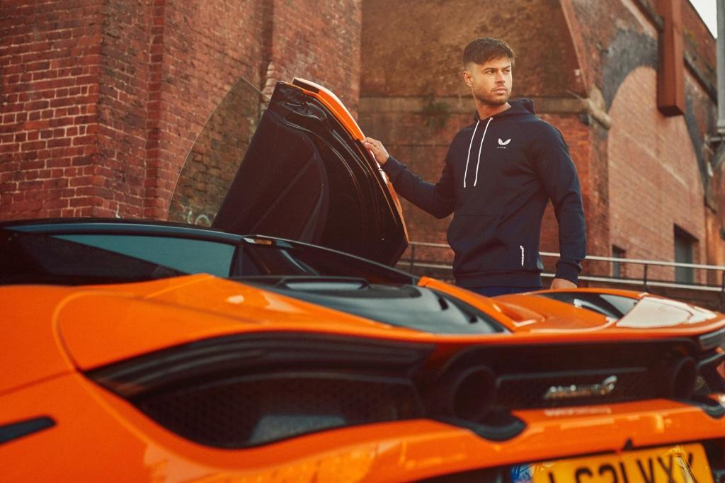 A mean wearing a Castore McLaren hoodie gets into a McLaren supercar