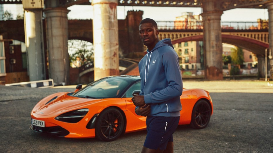 Athletic man stands in front of a McLaren supercar wearing Castore McLaren sportwear