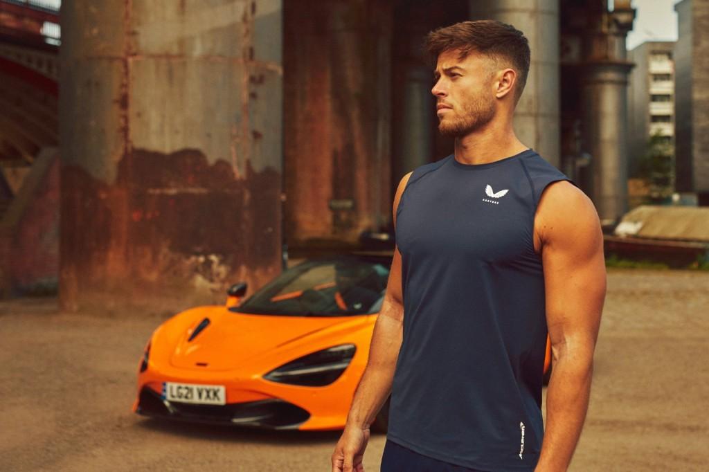 An athletic man wears a Castore McLaren vest in front of a McLaren supercar wearing