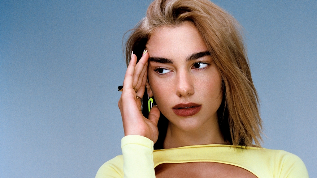 Singer Dua Lipa poses in a yellow dress for a promotional image
