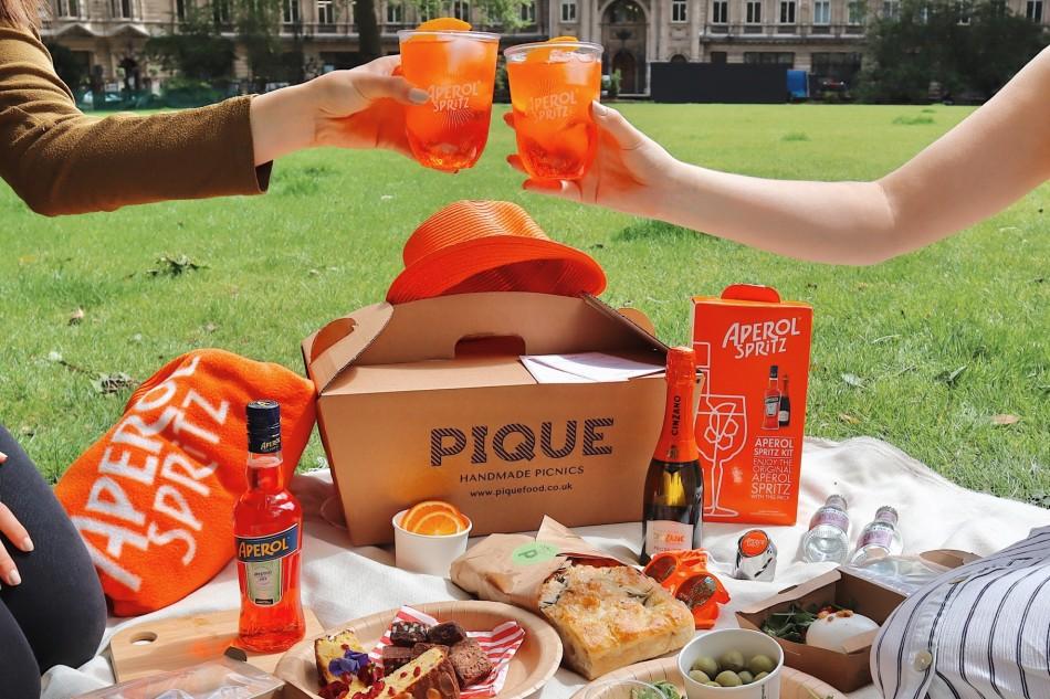 Aperol Spritz glasses clink at a picnic with Pique Handmade Picnics