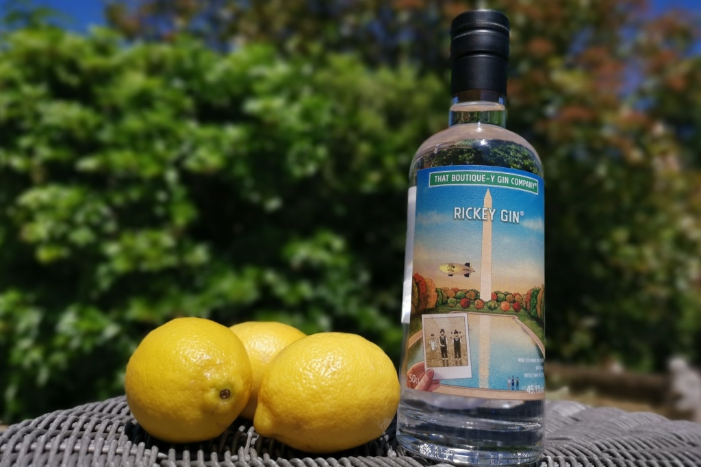 A bottle of Rickey Gin and a selection of lemons in a garden setting