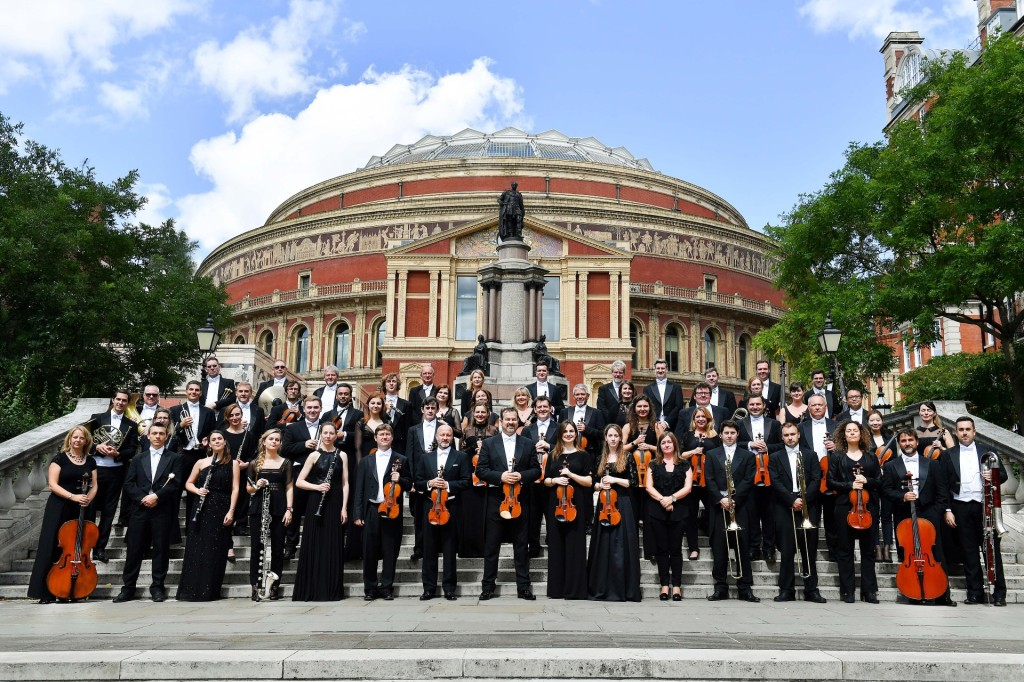 The Royal Philharmonic Orchestra stand on the steps outside the Royal Albert Hall