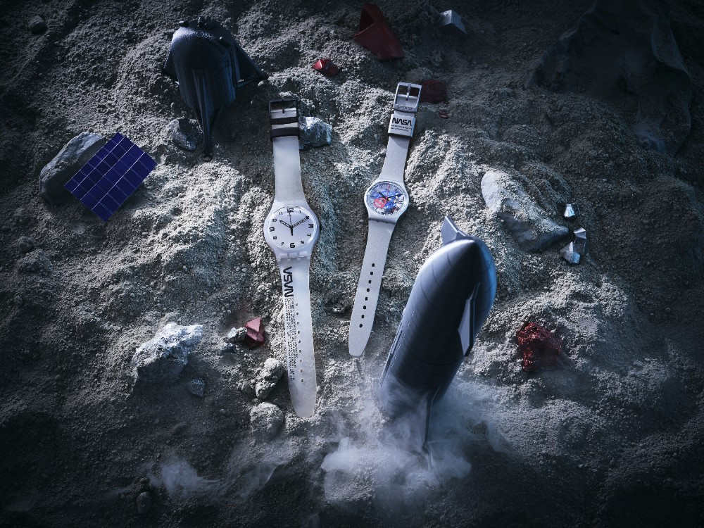 Two Swatch Space Collection watches sit alongside a rocket on a moon-like surface