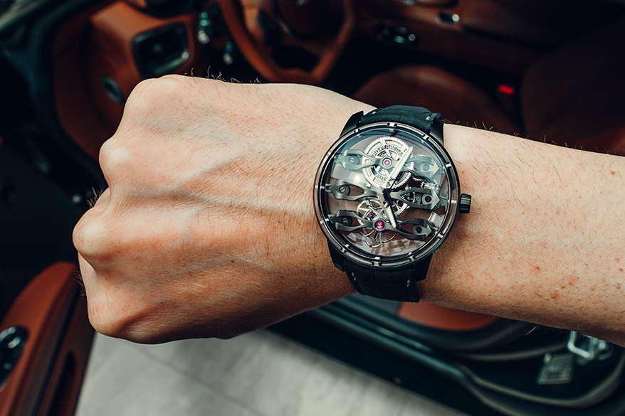 Close up of Aston Martin watch on a wrist with a car cabin in the background