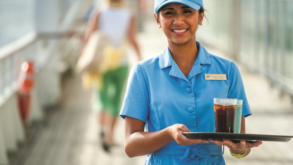 Waitress carrying carries a tray of drinks on a Fred Olsen cruise ship promenade