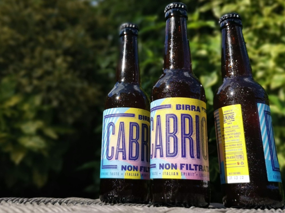 Three bottles of Birra Cabriole lager in a garden setting