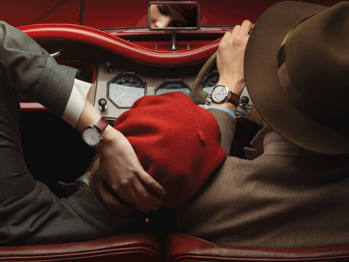 A couple in a classic car show off their luxury watches
