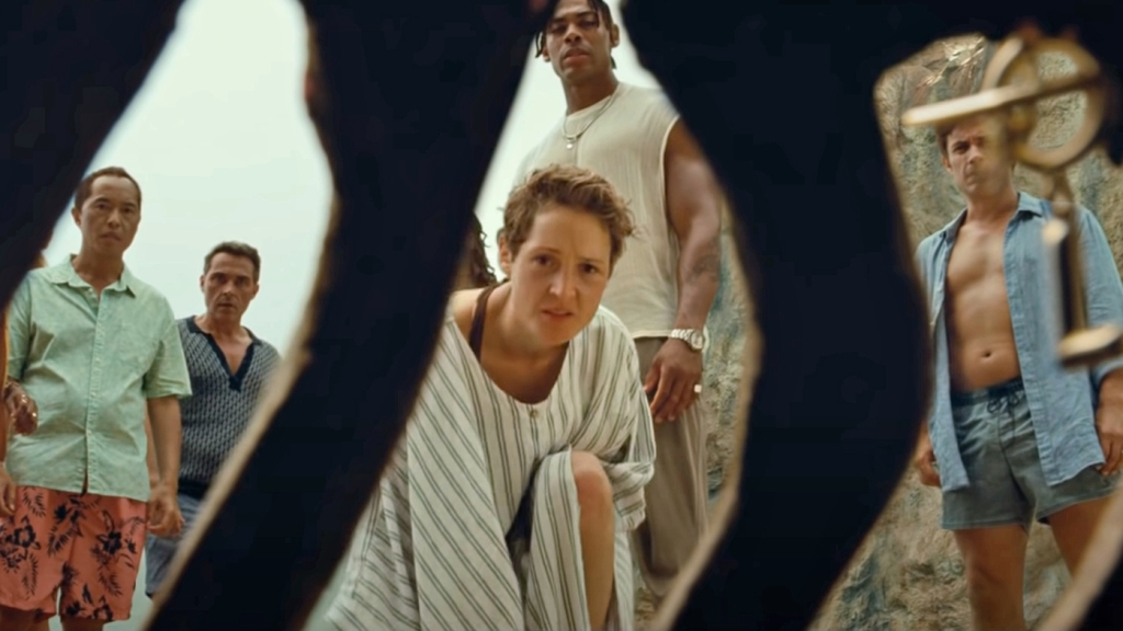 The cast of Old are framed by the ribs of a corpse on a beach in Old