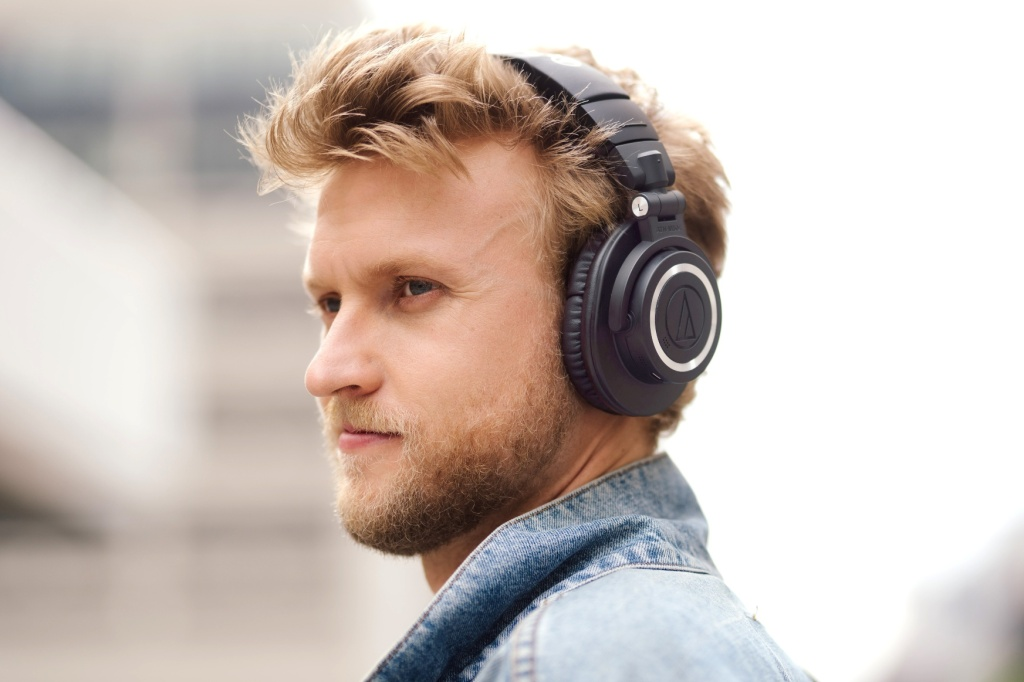 Audio Technica ATH-M50xBT2 headphones worn by a young man in a denim jacket