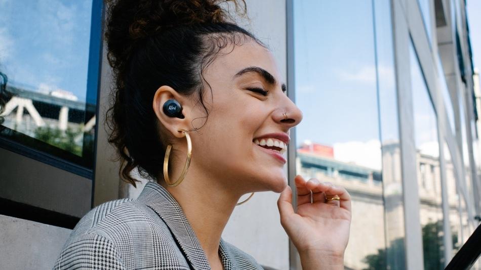 A yound woman wears Klipsch TN5 II earphones while taking a call