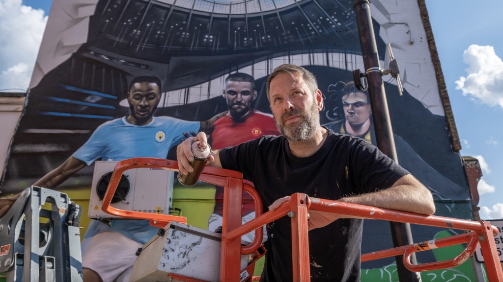 Street artist Jody Thomas poses paint can in hand in front of his football mural