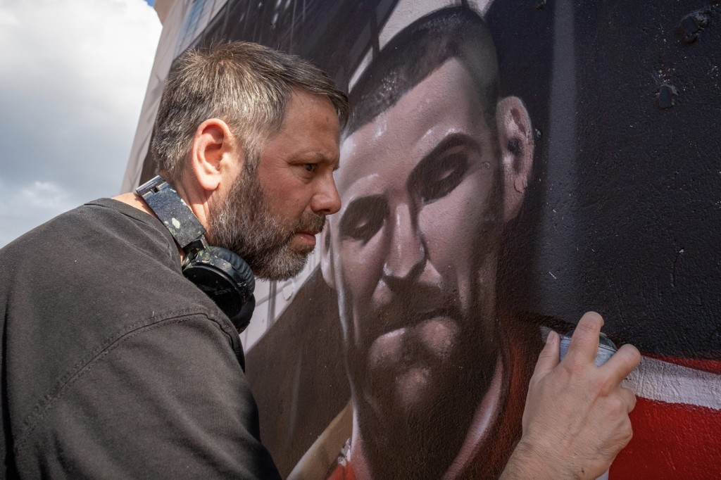 Artist Jody Thomas paints his football mural