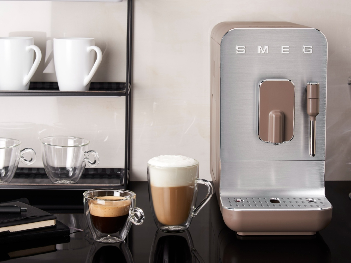 Smeg BCC02 bean-to-cup coffee machine on a kitchen worktop with coffee cup nearby