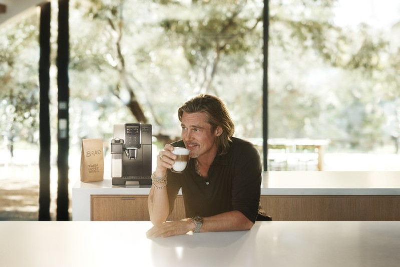 Brad Pitt poses in front of a De Longhi Dinamica coffee machine...