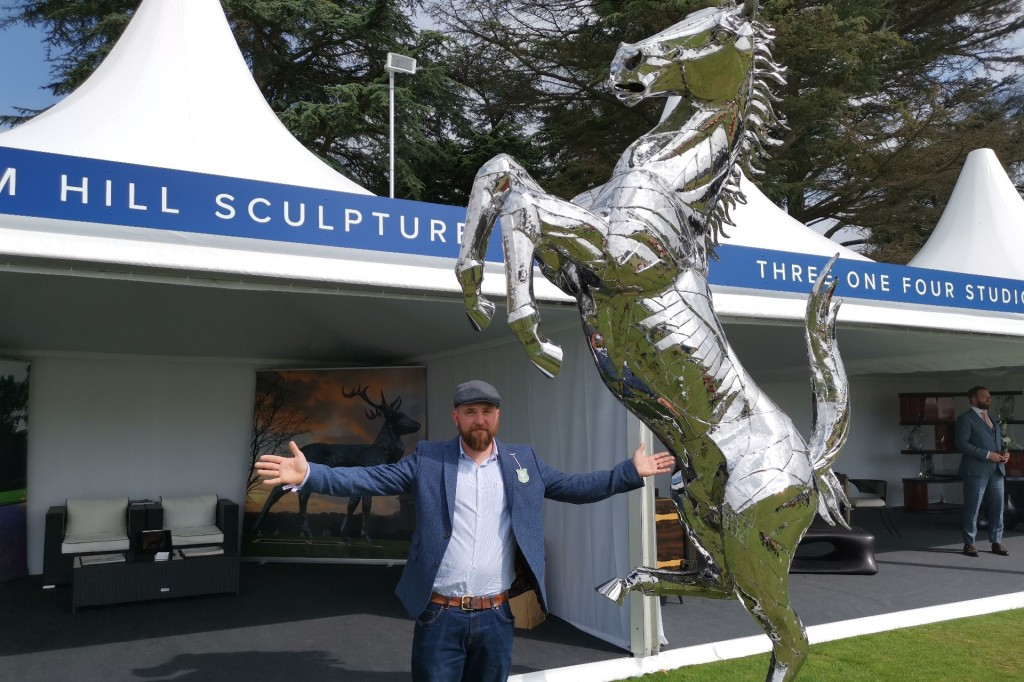 Sculptor Tom Hill at Salon prive in front of a big metal horse