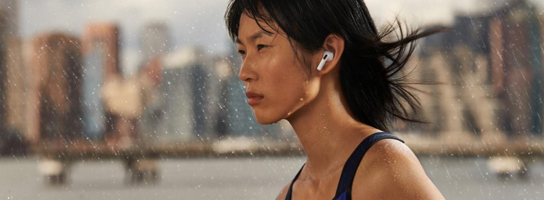 A runner wearing Apple AirPods 3rd Gen jogs through the rain