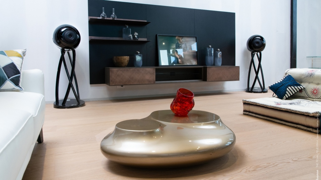 A pair of Cabasse Pearl Pelegrina speakers positioned either side of a small TV in a designer living room