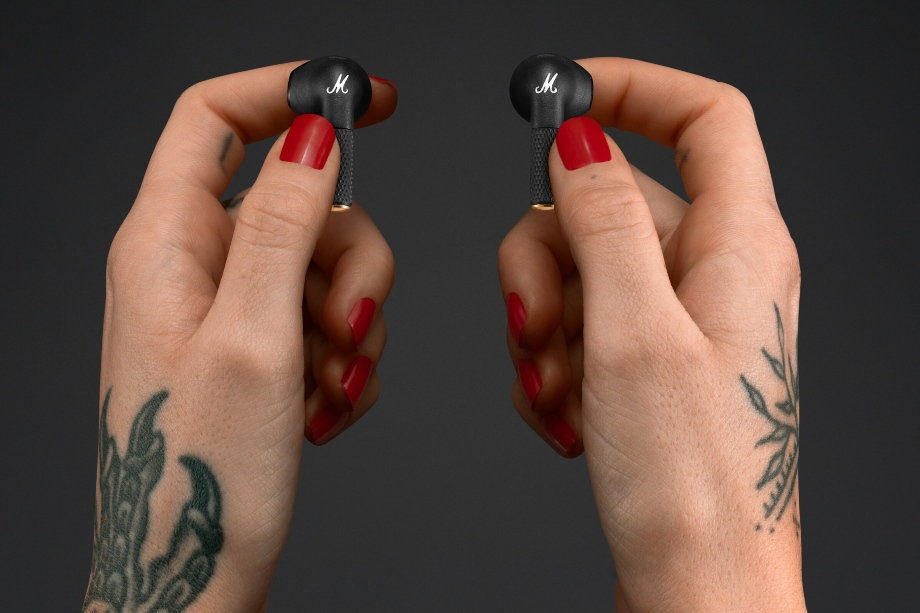 Marshall Minor III earbuds held in a pair of tattooed hands